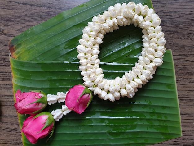 Estilo tailandés de guirnalda de jazmín en hojas de plátano y fondo de madera