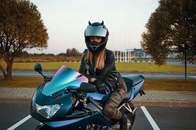Estilo de vida activo, extremo y concepto de adrenalina. retrato al aire libre de mujer rubia joven de moda con jeans caqui, casco de seguridad, guantes de cuero negro y chaqueta posando en motocicleta