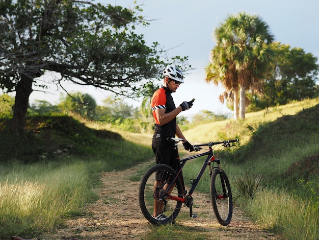 Estilo de vida activo. fotografía al aire libre del ciclista en bicicleta de montaña usando el navegador en el teléfono inteligente, explorando el mapa y buscando gps mientras anda en bicicleta en el campo.