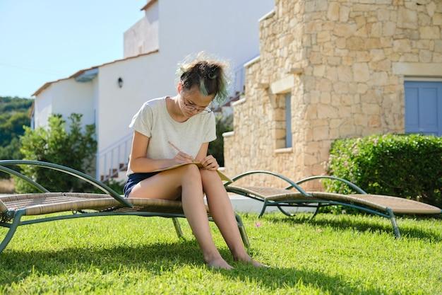 Estilo de vida de una adolescente de 15, 16 años, niña sentada en la tumbona de la silla de jardín sobre el césped, escribe estudiando en el cuaderno escolar. césped cerca de la casa, día de verano