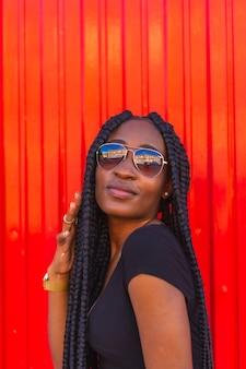 Estilo de vida chica negra con gran trenza en camiseta negra pantalones cortos de mezclilla y gafas de sol en una pared roja retrato de un joven bailarín de trampa
