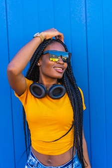 Estilo de vida, chica negra con largas trenzas, camiseta amarilla y gafas de sol. chica sexy y dj con auriculares sonriendo