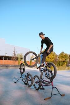 Estilo de vida de los ciclistas de bmx, entrenamiento en skatepark. deporte extremo en bicicleta, ejercicio de ciclo peligroso, paseos en la calle, adolescentes en bicicleta en el parque de verano