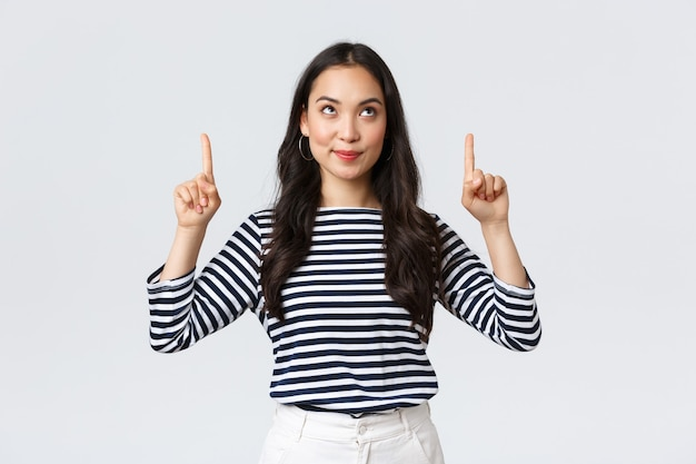 Estilo de vida, concepto de emociones de personas. emocionada chica asiática guapa sonriendo complacida al encontrar un producto excelente, apuntando con el dedo hacia el anuncio y luciendo satisfecha, recomendar promoción