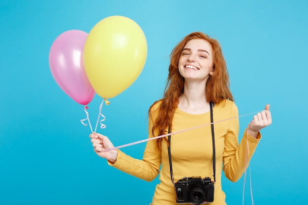 Estilo de vida y concepto de fiesta de cerca retrato joven hermosa atractiva pelirroja pelirroja con globos de colores y cámara vintage azul pastel espacio de copia de pared