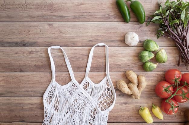 Estilo de vida sin desperdicio. bolsa de algodón con verduras frescas en la mesa de madera plana. libre de plástico para la compra y entrega de productos alimenticios.