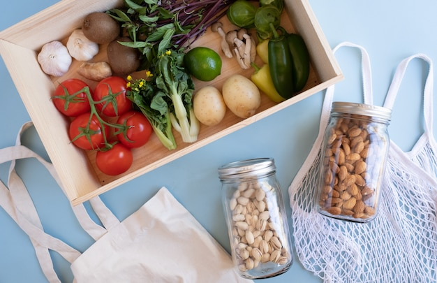 Estilo de vida sin desperdicio. bolsa de red de algodón con verduras frescas y tarro de cristal sostenible en mesa de madera plana. libre de plástico para la compra y entrega de productos alimenticios.