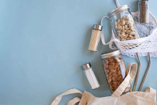 Estilo de vida sin desperdicios. bolsa de red de algodón con nuez, especias en frasco de vidrio sostenible y paja reutilizable sobre fondo azul.