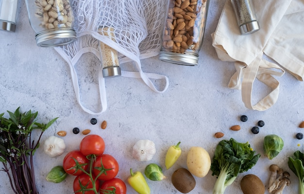 Estilo de vida sin desperdicios. bolsa de red de algodón con verduras frescas y tarro de vidrio sostenible sobre fondo plano de cemento. libre de plástico para la compra y entrega de productos alimenticios.