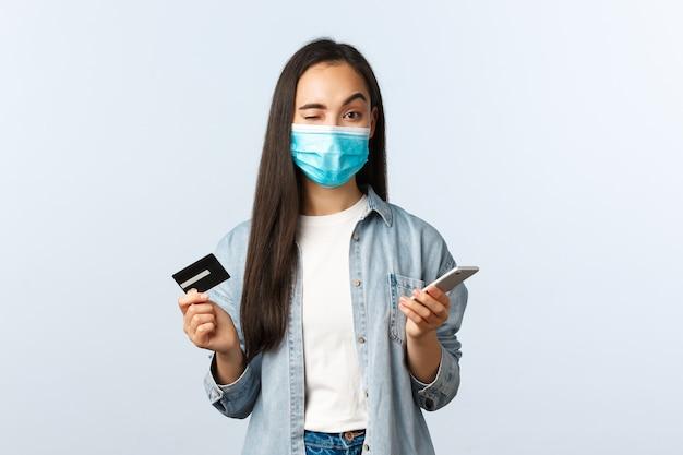 Estilo de vida de distanciamiento social, pandemia de covid-19 y concepto de compras sin contacto. la chica asiática linda descarada en la máscara médica anima a comprar en línea, guiña un ojo, sostiene la tarjeta de crédito y el teléfono inteligente