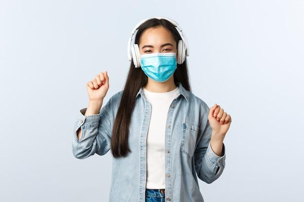 Estilo de vida de distanciamiento social, pandemia de covid-19 y concepto de ocio de autoaislamiento. chica asiática moderna sin preocupaciones con máscara médica, escuchando música con auriculares y bailando su canción favorita