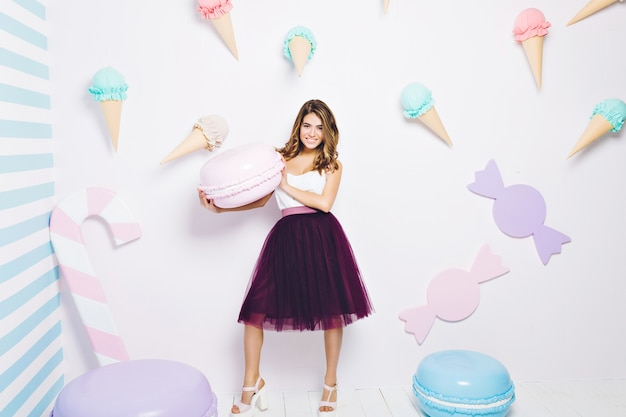 Estilo de vida dulce, expresando emociones positivas de mujer joven en falda de tul sosteniendo grandes macarrones alrededor de dulces. dulces, helados, felicidad, colores pastel.