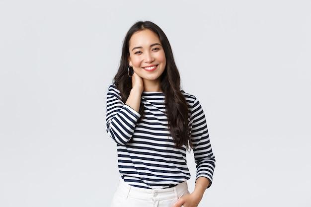 Estilo de vida, emociones de la gente y concepto casual. alegre hermosa mujer asiática en elegante ropa casual, toque el cuello sonrojándose y sonriendo, teniendo una pequeña charla en una cita romántica