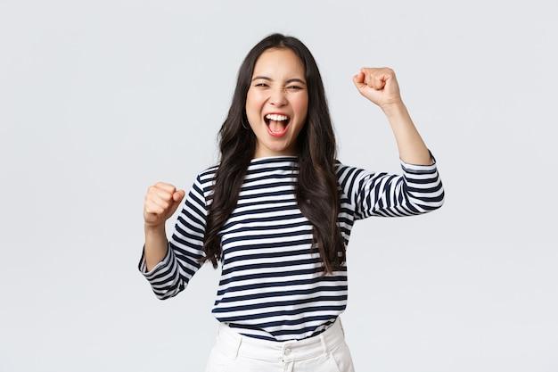 Estilo de vida, emociones de la gente y concepto casual. la mujer asiática feliz y emocionada asiste a la competencia deportiva, animando y cantando para el equipo, levantando las manos y gritando que sí.