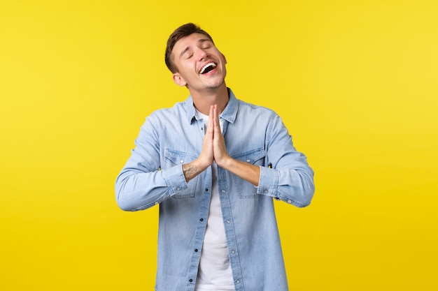 Estilo de vida, emociones de la gente y concepto de ocio de verano. esperanza encantado y aliviado apuesto hombre sonriente que se siente feliz, tomados de la mano en oración con los ojos cerrados y agradeciendo a dios, siendo agradecido.