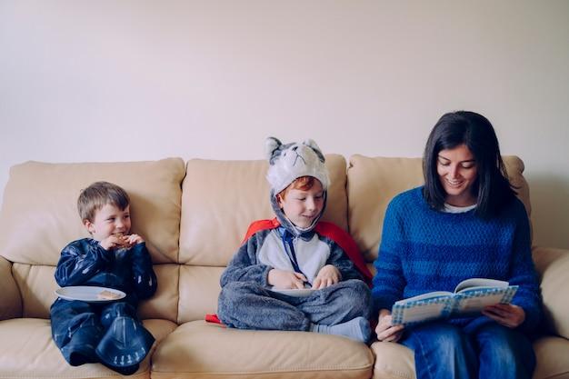 Estilo de vida familiar en interiores. joven madre leyendo un libro interesante a sus hijos vestidos con trajes de carnaval. cuentacuentos con mamá. los niños sin escuela pasan tiempo en casa en casa.