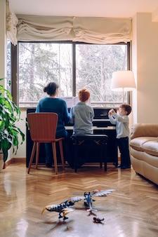 Estilo de vida familiar pasar tiempo juntos en el interior. niños con virtud musical y curiosidad artística. mamá enseñando a su hijo en casa lecciones de piano.