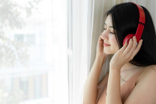 Estilo de vida hermosa mujer asiática linda niña sentirse feliz disfrutar escuchando música con auriculares auriculares en el dormitorio blanco