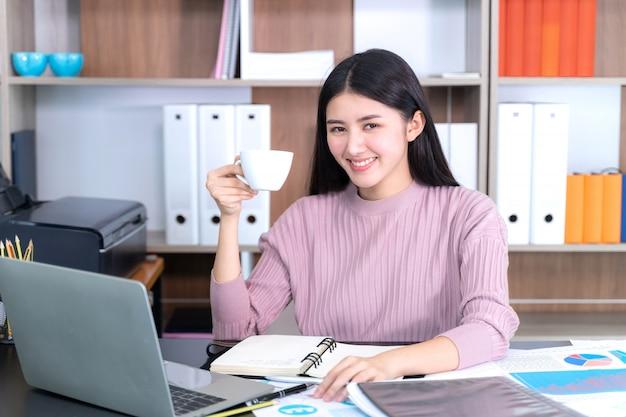 Estilo de vida hermosa mujer de negocios asiática joven en escritorio de oficina taza de café caliente en mano