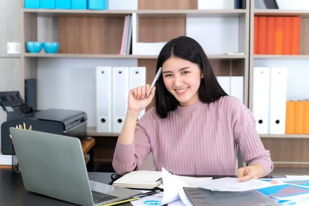 Estilo de vida hermosa mujer de negocios asiática joven usando la computadora portátil en el escritorio de oficina