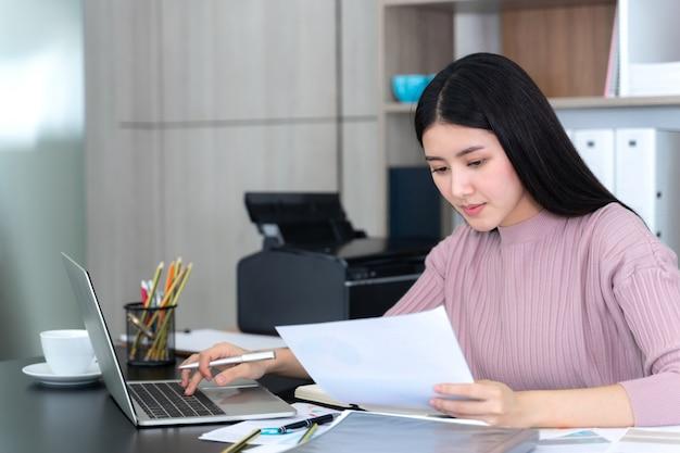 Estilo de vida hermosa mujer de negocios asiática joven usando la computadora portátil y el teléfono inteligente en el escritorio de oficina Foto gratis