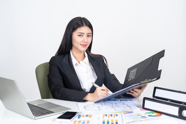 Estilo de vida hermoso negocio asiático joven mujer usando la computadora portátil y teléfono inteligente en el escritorio de oficina