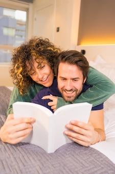 Estilo de vida, una joven pareja caucásica con miradas de complicidad, en pijama en la cama leyendo un bonito libro abrazando