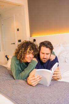 Estilo de vida, una joven pareja caucásica, en pijama en la cama leyendo un libro agradable abrazado