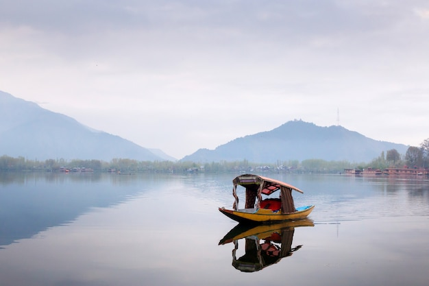 Estilo de vida en el lago dal, el hombre conduce el bote en medio del lago dal y el fondo de la montaña
