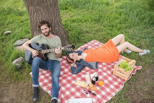 Estilo de vida. linda chica joven feliz en vestido descansando sobre cuadros y chico barbudo tocando la guitarra en el parque en un día cálido