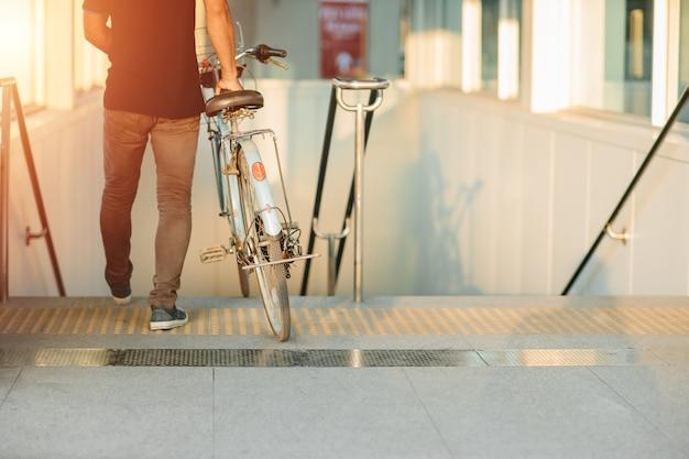 El estilo de vida moderno de la gente urbana que usa traer bicicletas va con la estación de tren subterráneo del metro en un día sin automóviles.