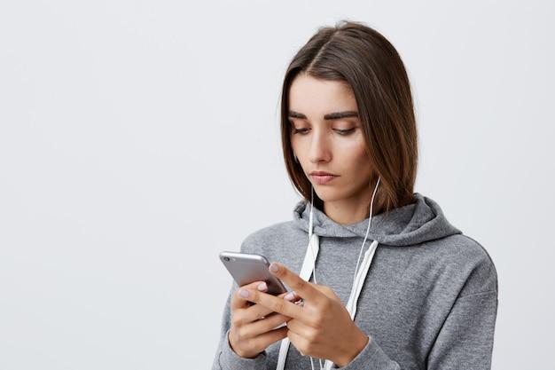 Estilo de vida moderno. retrato de joven hermosa encantadora estudiante caucásica chica con cabello largo y oscuro con capucha gris mirando en teléfono inteligente con expresión seria y tranquila, mirando a través de las redes sociales