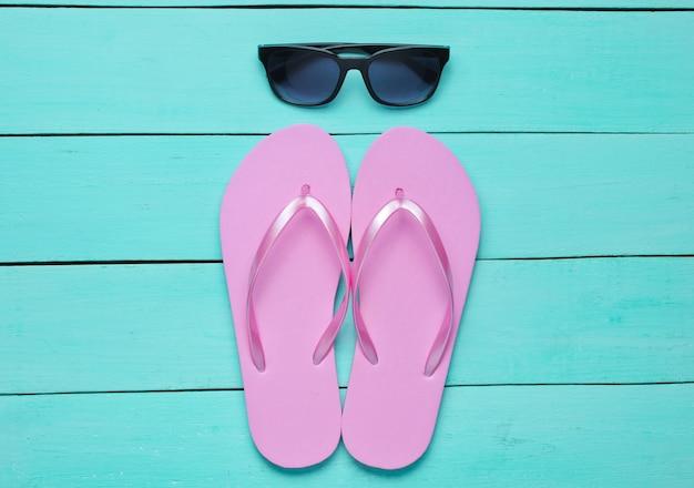 Estilo de vida de playa tropical. chanclas y gafas de sol sobre fondo de madera azul. fondo de verano. vista superior