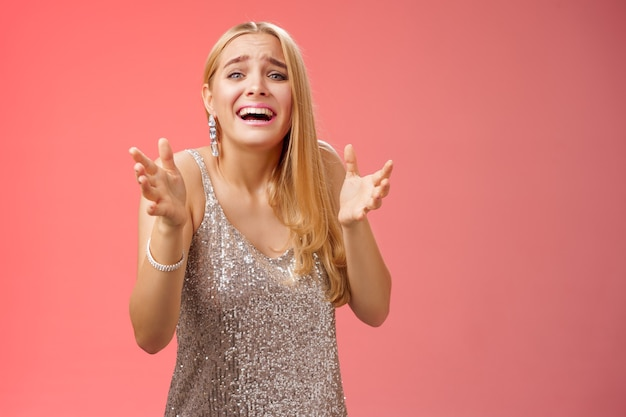 Estilo de vida. presa del pánico molesto miserable chica rubia con el corazón roto llorando levantando las manos pidiendo que no vaya novio roto mira tristeza angustiada freak-out de pie devastado fondo rojo durante la fiesta.