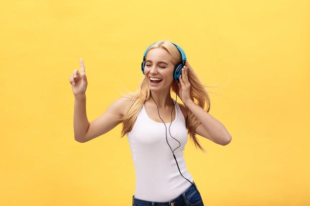 Estilo de vida retrato de una música que escucha de la mujer feliz en los auriculares aislados en un fondo amarillo
