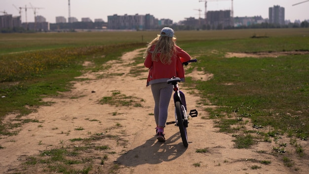 Estilo de vida saludable - chica con una bicicleta caminando en un campo cerca de la ciudad