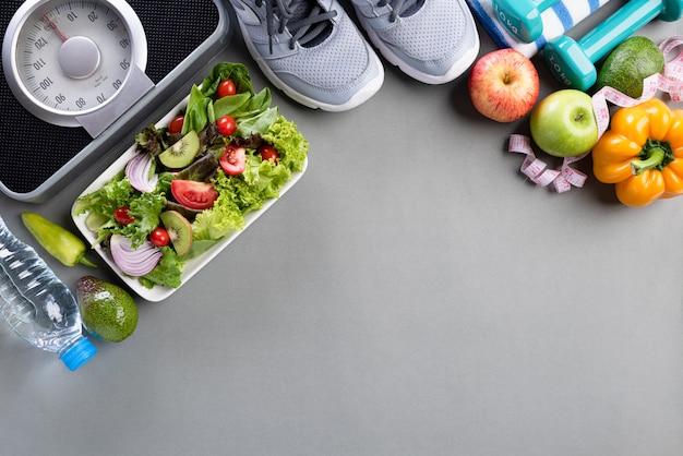Estilo de vida saludable, comida y deporte concepto en gris.
