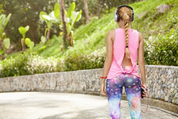 Estilo de vida saludable y comunicación moderna. vista trasera de una chica deportiva en ropa deportiva y grandes auriculares de pie en la carretera, utilizando tecnología de teléfono inteligente para escuchar música durante la carrera.