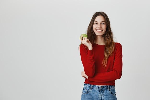 Estilo de vida saludable y concepto deportivo. mujer atractiva sonriente que come la manzana