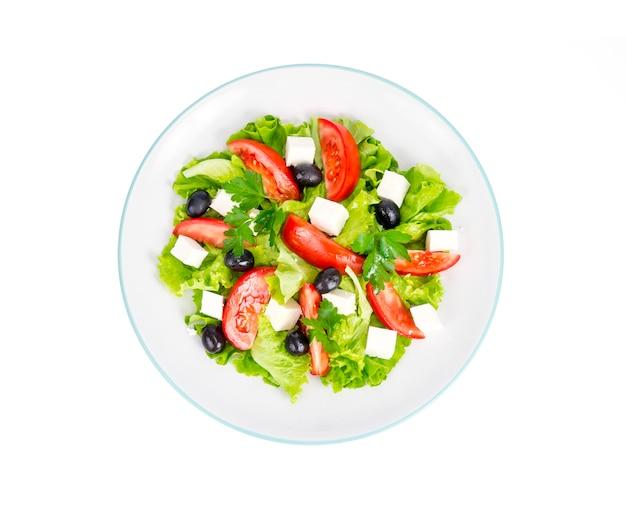 Estilo de vida saludable. ensalada de dieta vegetal con aceitunas y queso de cabra sobre fondo blanco.