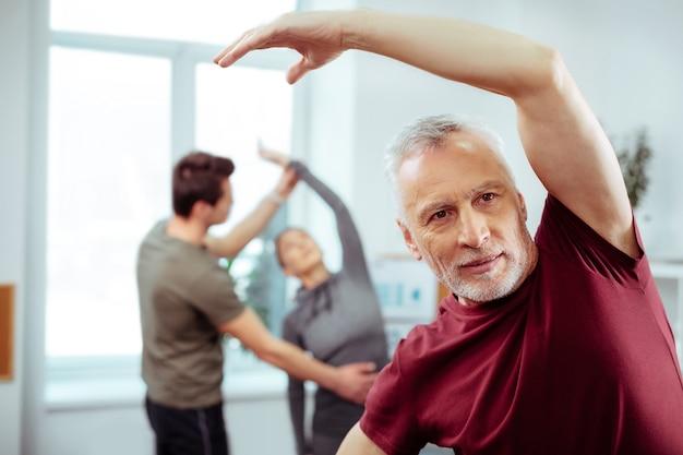 Estilo de vida saludable. hombre maduro guapo haciendo ejercicio mientras intenta estar en forma