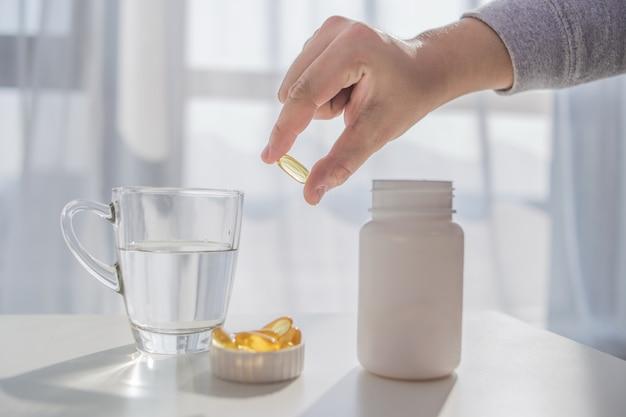 Estilo de vida saludable, la medicina, los suplementos nutricionales y el concepto de la gente - cerca de las manos masculinas celebración de píldoras con cápsulas de aceite de hígado de bacalao y vidrio de agua