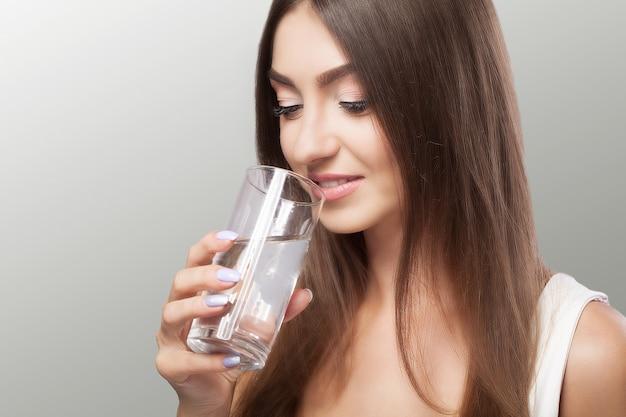 Estilo de vida saludable. retrato de mujer joven sonriente feliz con vaso de agua dulce. cuidado de la salud. bebidas salud, belleza, dieta.