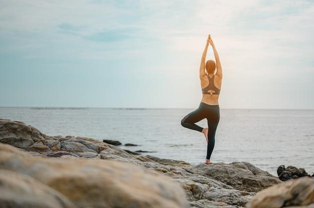 Estilo de vida saludable yoga mujer practicando yoga meditación y energía equilibrada en las piedras cerca del mar