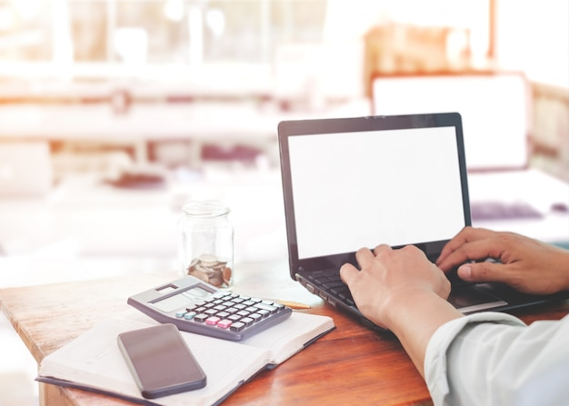 El estilo de vida de los trabajadores de oficina - manos de empresario joven escribiendo en su computadora portátil. hombre de negocios que trabajan en la oficina de negocios moderno para las finanzas y los impuestos con la taza de café rojo. filtro del color de la vendimia.