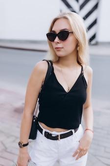 Estilo de vida urbano moda retrato de moda de joven linda chica rubia vestida con ropa en blanco y negro caminando en la ciudad en día de verano