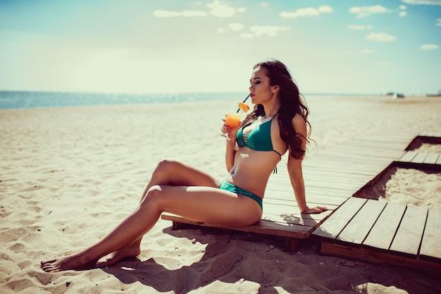 Estilo de vida de verano hermosa mujer joven despreocupada feliz relajante en la playa al atardecer