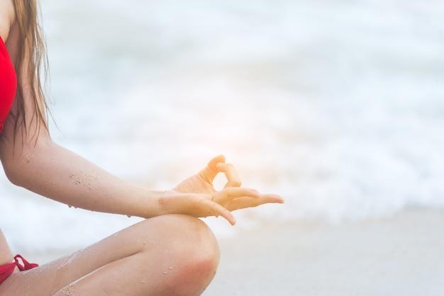 Estilo de vida de yoga fitness en la playa mujer sana relajación haciendo meditación. yoga meditando al aire libre con zen en posición sentada. concepto de ejercicio de concentración de felicidad joven de fitness de iluminación