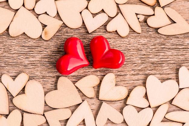 Estilo vintage de dos corazones rojos con corazones de madera sobre un fondo de madera.