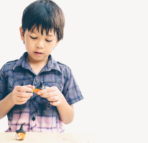 El estilo vintage de un niño encantador asiático está jugando la arcilla de halloween alegremente